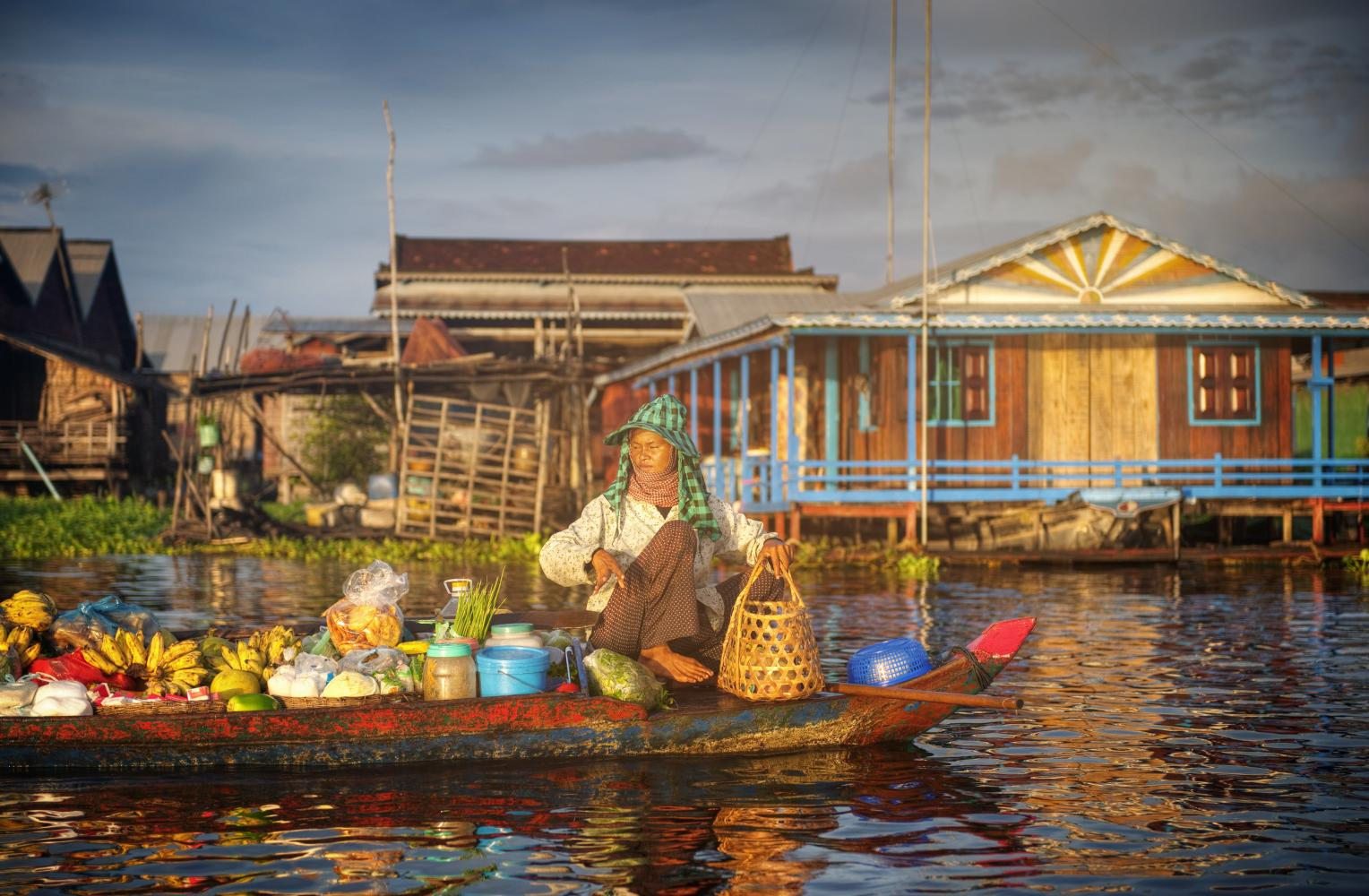 Woman selling fruits on a boat to symbolise basic commerce before the digital age.